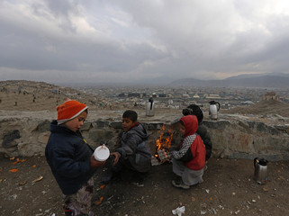 Afghan children, who are selling tea, warm themselves by a fire on a cold day in Kabul