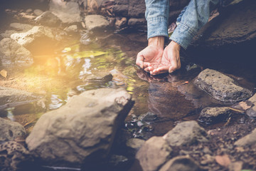 Water in the hands of women. Woman taking clear water in the Small stream hands