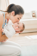side view of beautiful mother kissing and hugging baby child at home
