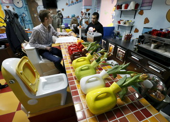 Flower vases designed in likeness of urinals are seen on counter at Crazy Toilet Cafe in central Moscow