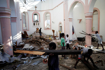 People clear a church from debris after Hurricane Matthew in Les Anglais