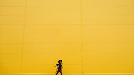 Woman at yellow wall