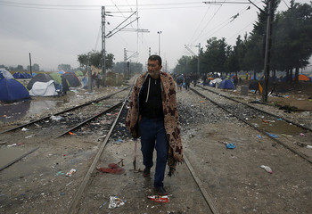A Syrian refugee man walks close to the border between Greece and Macedonia