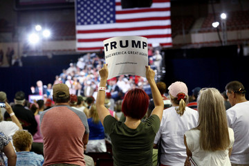 A woman holds up a campaign sign as Republican U.S. Presidential candidate Donald Trump speaks at a rally in Phoenix