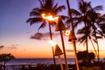 Fototapeten Braun Hawaii sunset with fire torches. Hawaiian icon, lights burning at dusk at beach resort or restaurants for outdoor lighting and decoration, cozy atmosphere.