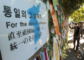 A South Korean tour guide does an introduction to tourists as she points out a barbed wire fence on which South Korean flags and reunification ribbons are hung, at Imjingak pavilion near the demilitarized zone in Paju