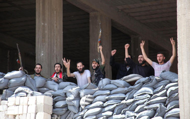 Soldiers loyal to Syria's President Assad pose for a photo in Aleppo's main prison