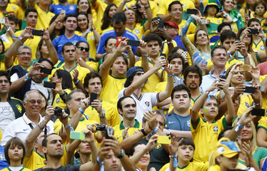 Fans take pictures at the 2014 World Cup Group A soccer match between Cameroon and Brazil at the Brasilia national stadium