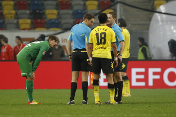 Referees discuss with Borusia Dortmund's Barrios after their supporters have thrown pyrotechnics during the 'Winter Soccer Cup 2012' against Werder Bremen in Duesseldorf