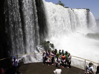 Tourists pose for photos with Iguazu Falls in the background from an observation platform at the Iguazu National Park