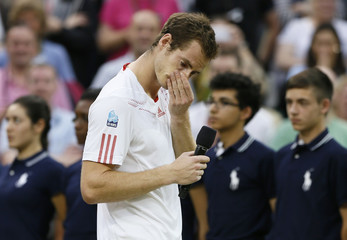 Andy Murray of Britain reacts during a television interview with Sue Barker after being defeated by Roger Federer of Switzerland in their men's singles final tennis match at the Wimbledon Tennis Championships in London