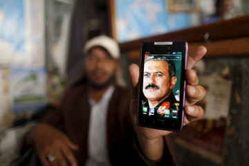 Man displays a picture of Yemen's former President Ali Abdullah Saleh on his mobile phone as he sits at a barber shop in the old quarter of Sanaa, Yemen