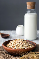 Oats and milk. Rolled oats or oat flakes and bottle of milk on background. Concept of healthy lifestyle, healthy eating