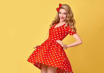 Fashion Beauty. PinUp Sensual Blond Girl Smiling in Red Polka Dots Summer Dress. Glamour Playful Woman on Yellow. Trendy Stylish Curly hairstyle, fashion Makeup, red Bow. Expressive facial expression