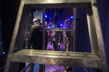 Ladder frames window display advertising men's fashion and decorated with holiday ornaments inside Saks Fifth Avenue store in New York, during preparations for scheduled unveiling of store's holiday windows