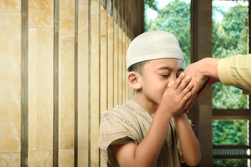 Asian muslim kid kissing his parent hand as respect symbol