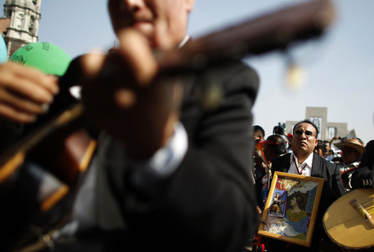A mariachi holds an icon of Saint Cecilia as colleagues play guitar during a pilgrimage to the Basilica of Our Lady of Guadalupe in Mexico City