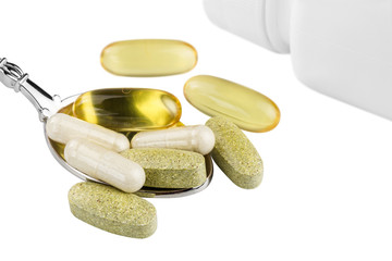 Vitamin complex, omega 3, glucosamine capsules, multivitamin supplements in the spoon and white container isolated on white background