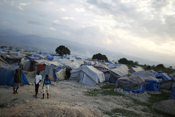 Haitians made homeless in the 2010 earthquake stand outside their tents on the outskirts of Port-au-Prince