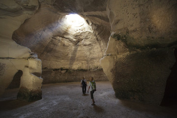 Visitors walk inside a cave situated below the ancient towns of Maresha and Beit Guvrin in the Judean Lowlands