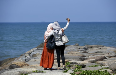 Visitors to the coastline take pictures facing the Indian Ocean a day after a 7.8 magnitude quake struck far out at sea in Padang, West Sumatra province, Indonesia