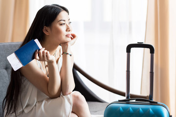 asian woman traveler sitting on sofa with suitcase and passport, packing luggage