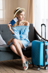 caucasian woman traveler sitting on sofa with suitcase and passport, packing luggage