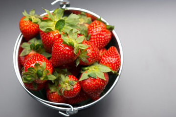 Strawberries in an aluminum bucket on black
