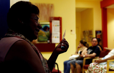 Paula, who asked to have her last name withheld, holds a membership card to the DC Health Care Alliance, as she is interviewed near the waiting room of the La Clinica Del Pueblo community health clinic in Washington