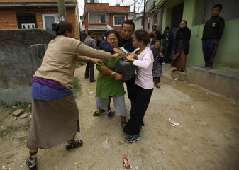 A Tibetan woman is stopped by her friends as she tries to self immolate herself after an argument with police personnel during a protest in Kathmandu