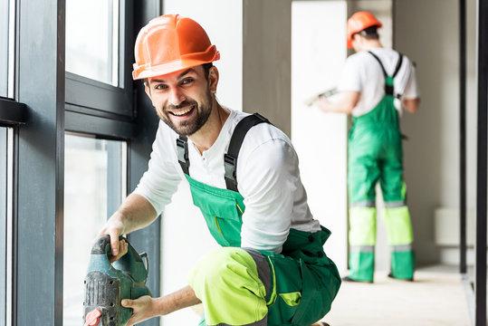 Hilarious smiling builder keeping tool