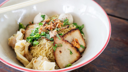 Noodles with pork on a wooden background (Thai noodles).