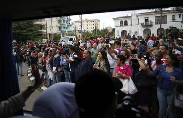 Cubans line the road to see the motorcade of U.S. President Barack Obama in Havana