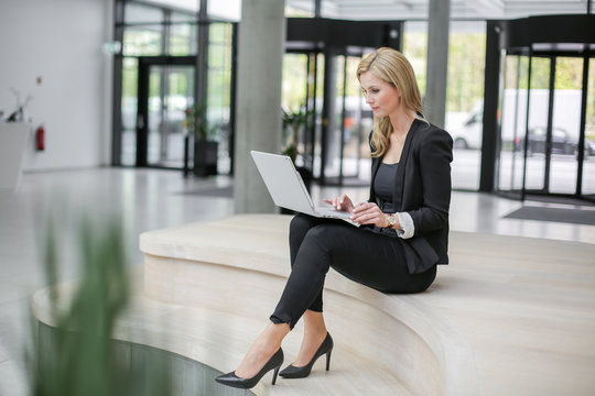 Young beautiful business woman sitting in a light an spacious office lobby using a laptop