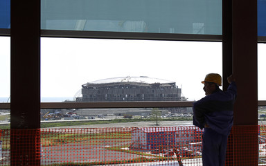 A worker looks on, with the under-construction Bolshoi Ice Palace seen in the background, in the Olympic park in Imeretinskaya Valley
