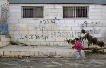 A Palestinian girl runs past graffiti sprayed on a house in village near Ramallah