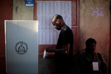 A man casts his ballot as a poll watcher licks a lollipop at a polling station at the Market of Canape Vert in Port-au-Prince