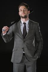 Serious young businessman holding baseball bat and looking at camera