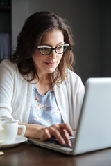 Smiling mature woman working on laptop at the table indoors