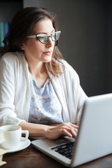 Mature woman working on laptop and having cup of tea