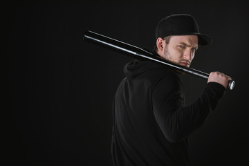 young robber in zoodie and cap with baseball bat isolated on black