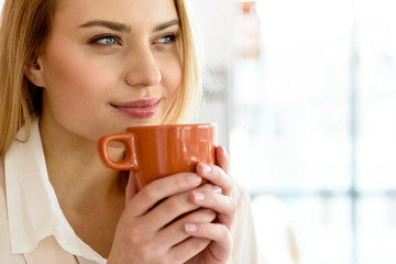 Charming young woman keeping cup of hot drink