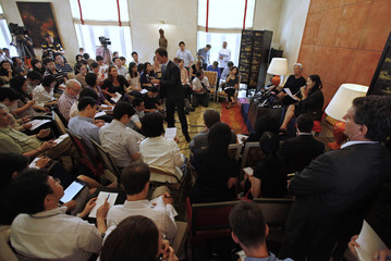 Journalists take notes during a press conference held by French Finance Minister Christine Lagarde at the French ambassador's residence in Beijing
