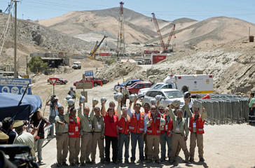 Chile's Mining Minister Golborne poses with members of the rescue team during a news conference at the San Jose mine in Copiapo