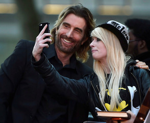 """Sharlto Copley poses for a photograph with a fan as he arrives for the gala screening of the film """"Free Fire"""", during the 60th British Film Institute (BFI) London Film Festival at Leicester Square in London"""