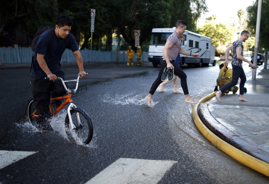 People take their shoes off to wade through water flooding a street near a major water main break on Sunset Boulevard in West Hollywood