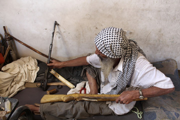 Abou al-Eizz al-Saour fixes a wooden frame for a weapon in his room in Duma neighbourhood, in Damascus