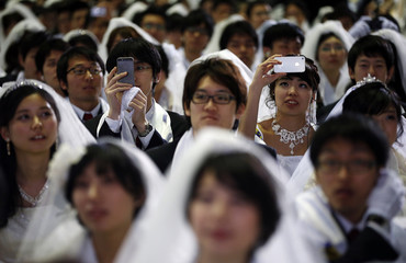 A newlywed couple takes photographs as they attend a mass wedding ceremony of the Unification Church at Cheongshim Peace World Centre in Gapyeong