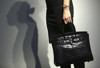 An assistant poses with a Hermes handbag, a Star of Sierra Leone 968.9 carat diamond ring and a 7.13 carat diamond Cartier bracelet, at Christie's auction house in London
