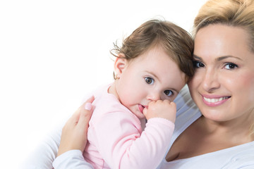 Mom and baby little girl hugging and looking at camera.White background.Copy space.Shallow doff